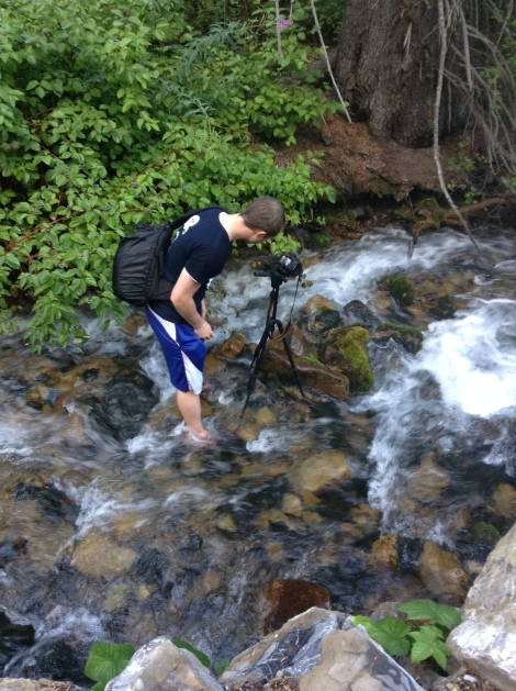 Photographer Laren Helms standing in the river below Stewart Falls.